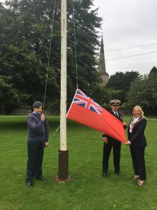 Photo of cadet raising Red Ensign