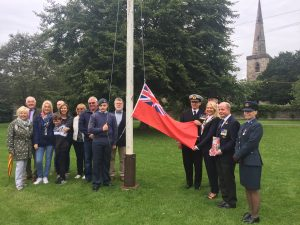 Photo of council and guests about to raise Red Ensign